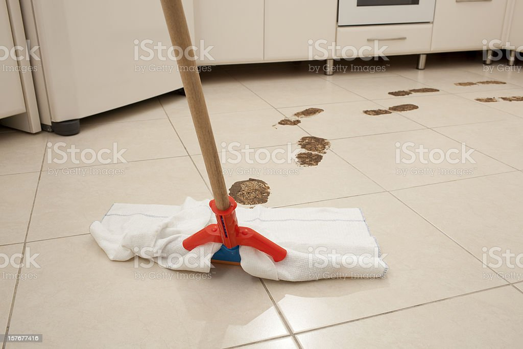 Muddy footprints cleaning by using mop on kitchen tiled floor.