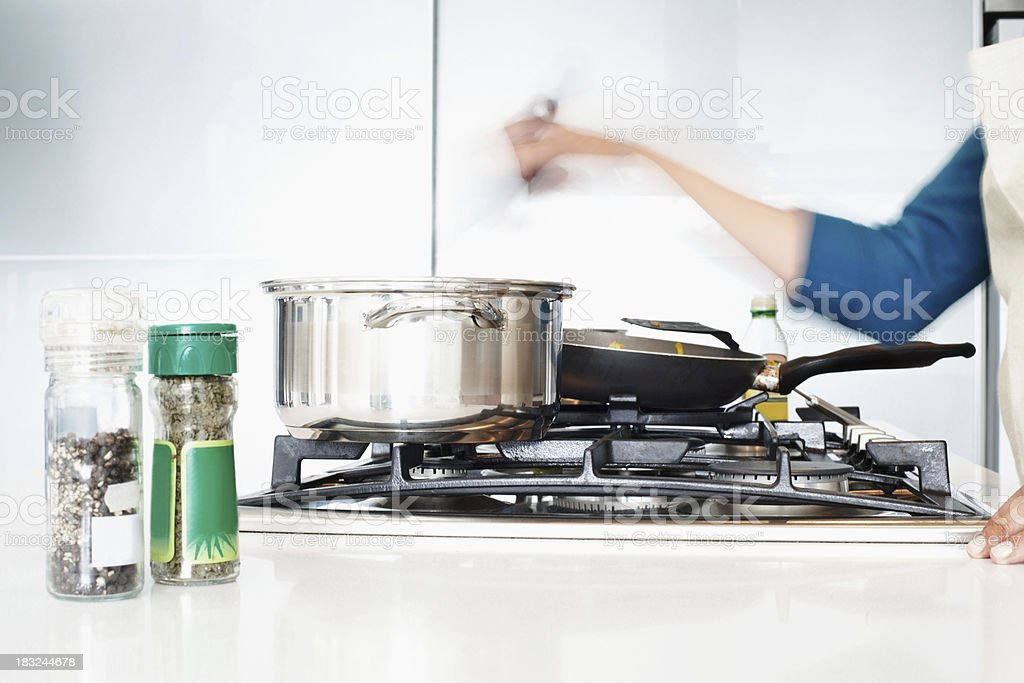 Kitchen hob with utensils and blurred motion of hand stirring stock photo
