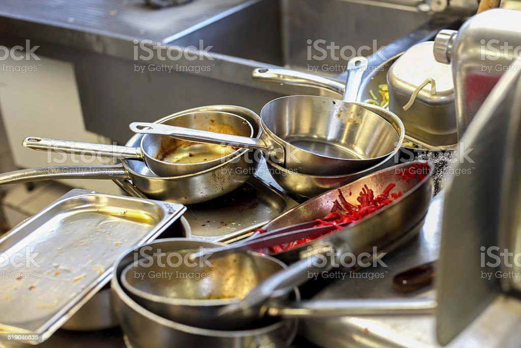 Kitchen in restaurant, sink filled with dirty metal dishes stock photo
