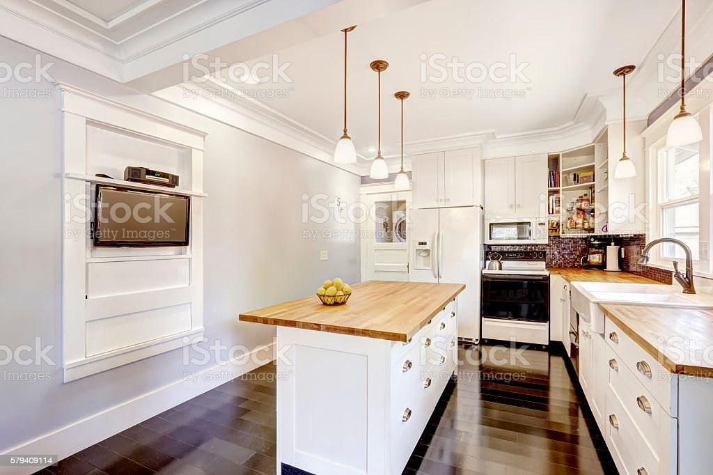 Kitchen interior in white tones with hardwood counter tops. stock photo