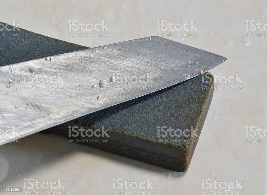 kitchen knife blade and whetstone on tile floor stock photo