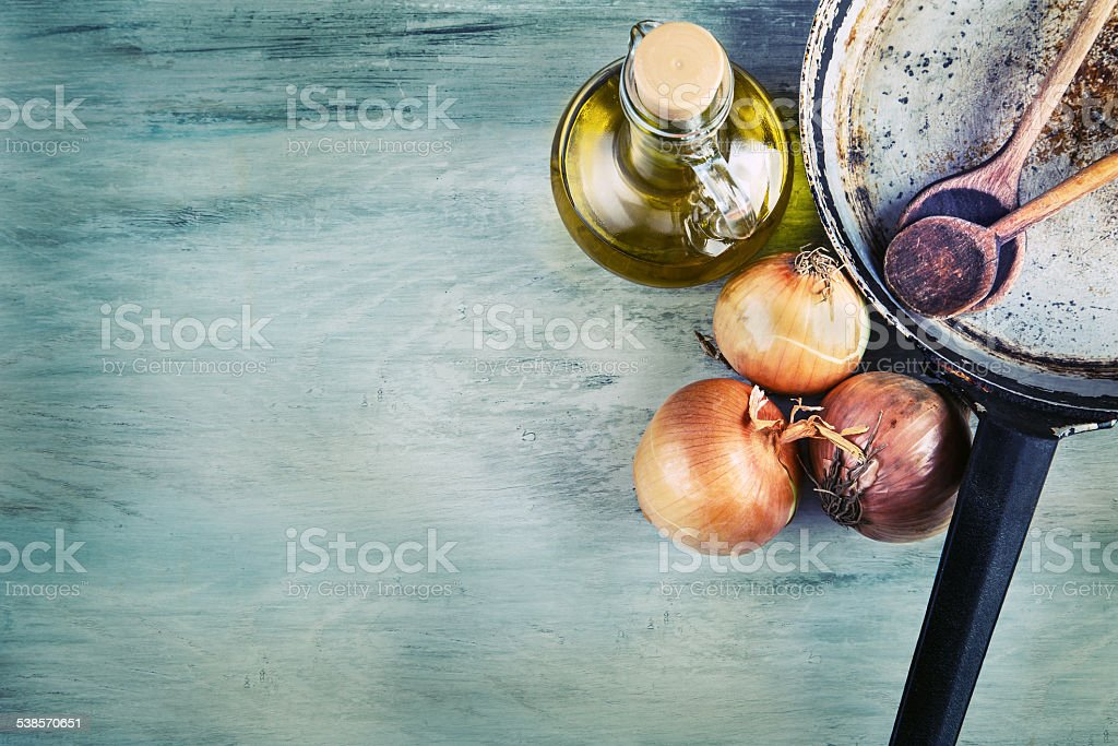 Kitchen pan wooden spoon three onions carafe with olive oil stock photo
