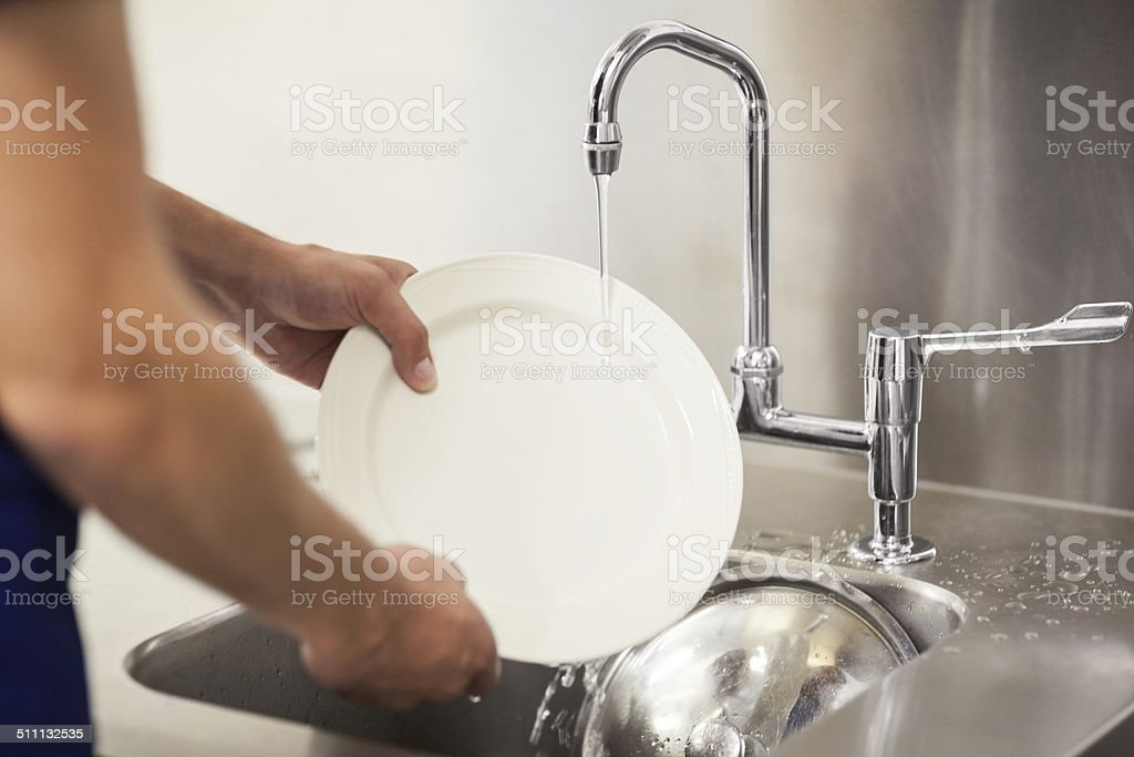 Kitchen porter cleaning white plates in sink stock photo