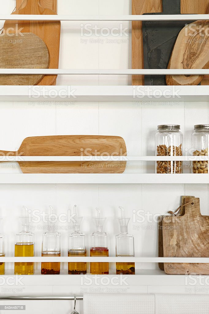 Kitchen rackets cabinets with oil bottles and accessories stock photo