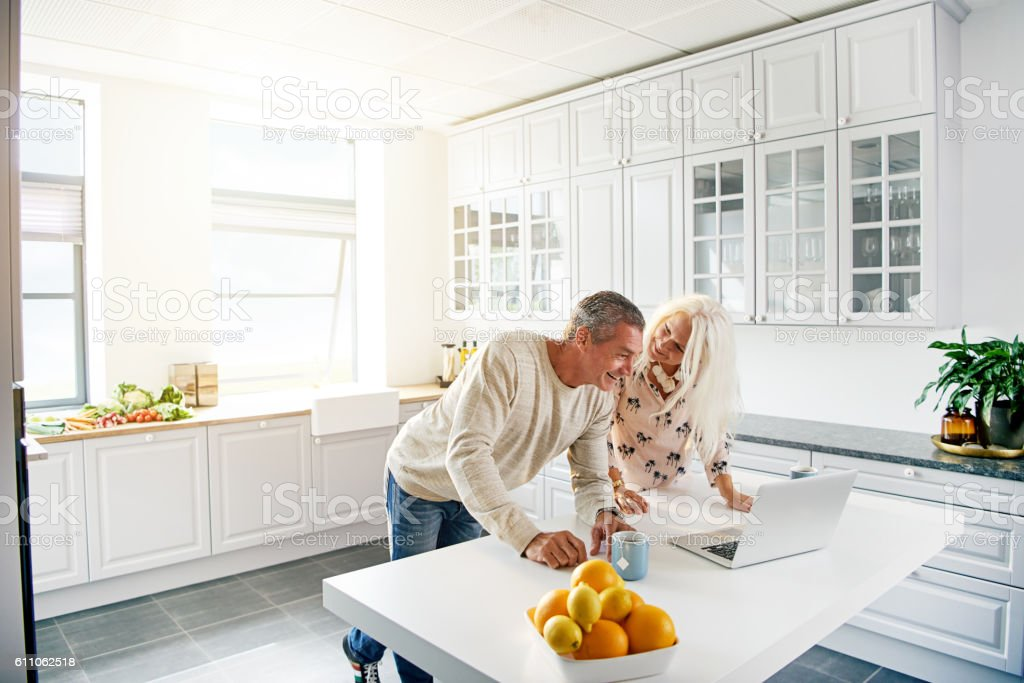 Kitchen scene with couple looking at computer stock photo