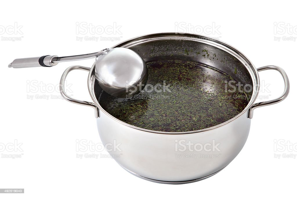 Kitchen spoon of metal leaned on a pot of soup. stock photo