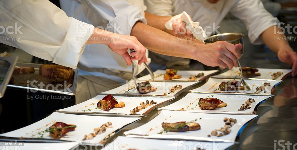 Kitchen staff and chef preparing gourmet meals for a party stock photo