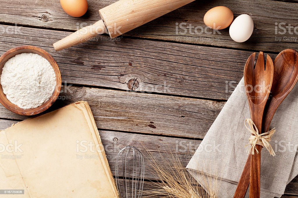 Kitchen table with cookbook, utensils and ingredients stock photo