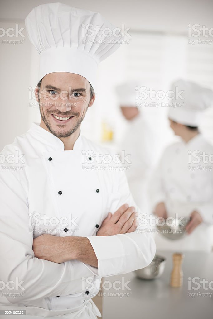 kitchen team at work female chef on foreground stock photo