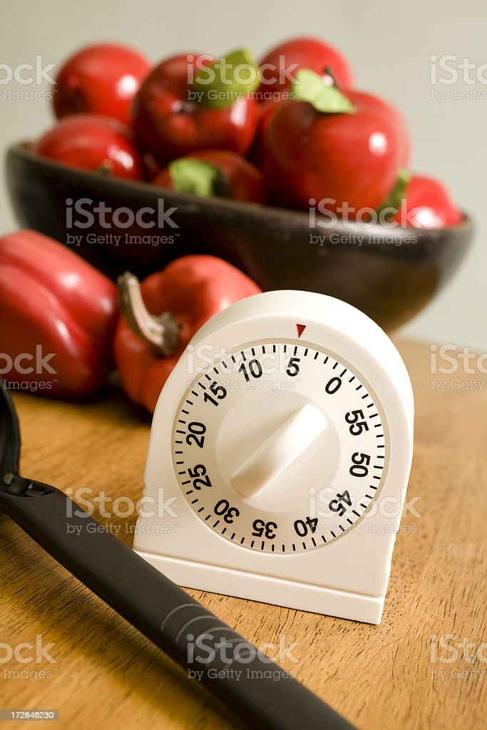 Kitchen timer on counter with bowl of apples and peppers stock photo