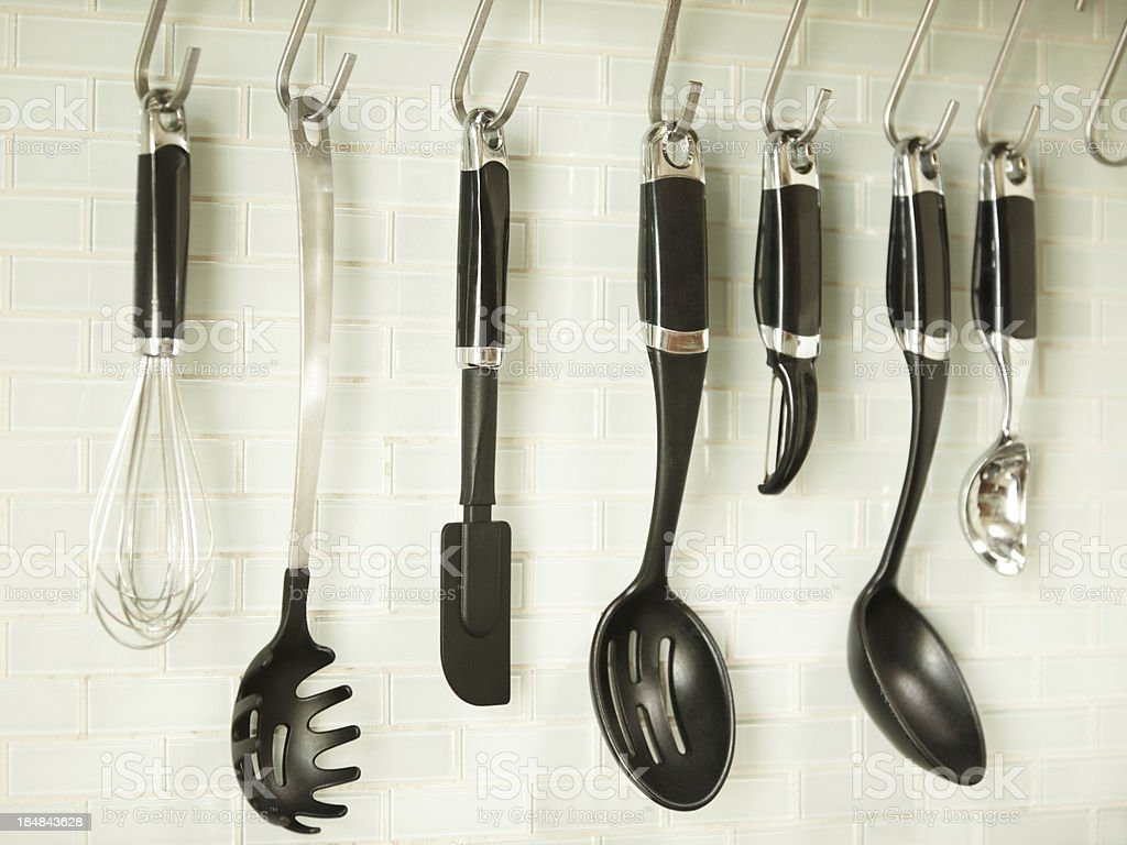 Kitchen utensils hanging on a white tile wall royalty-free stock photo