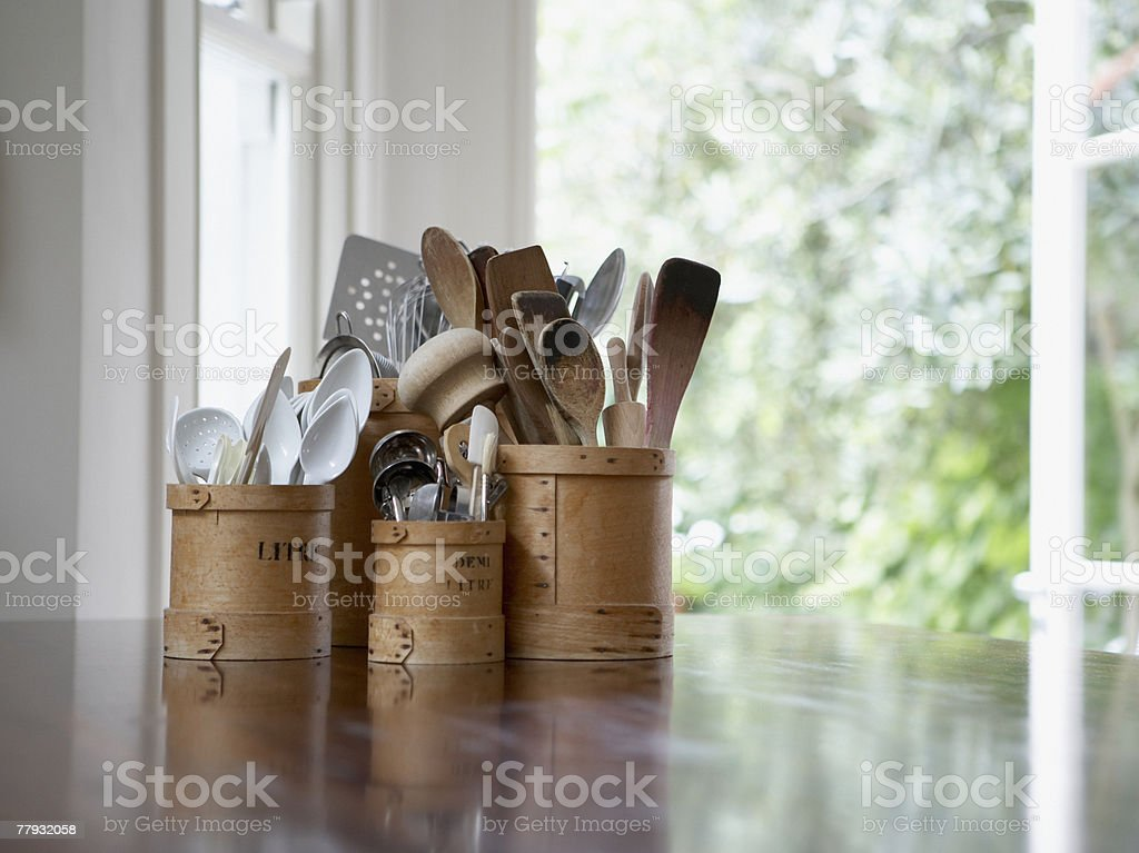 Kitchen utensils in containers on table stock photo