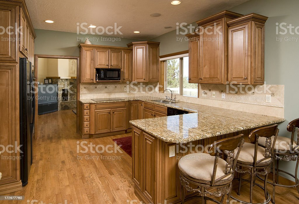 Kitchen with modern counters, stools and wood floors royalty-free stock photo