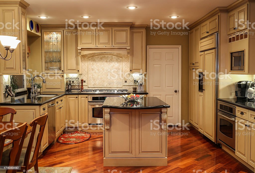 Kitchen wth oak wood cabinets island and granite countertops stock photo