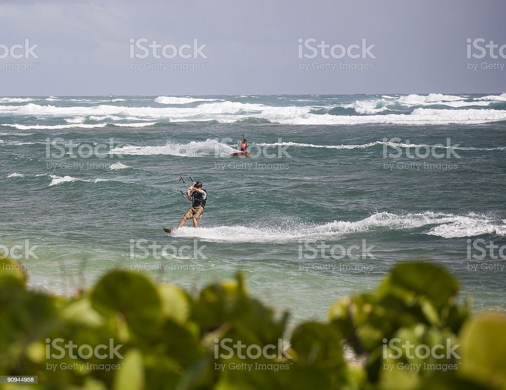 Kite boarders crossing paths with green foreground royalty-free stock photo