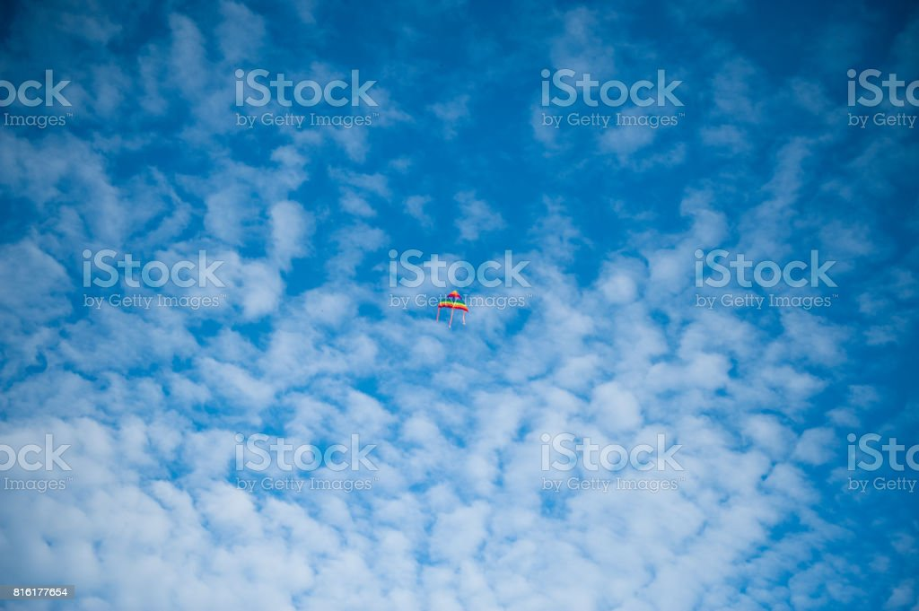 Kite flying in a blue cloudy sky stock photo
