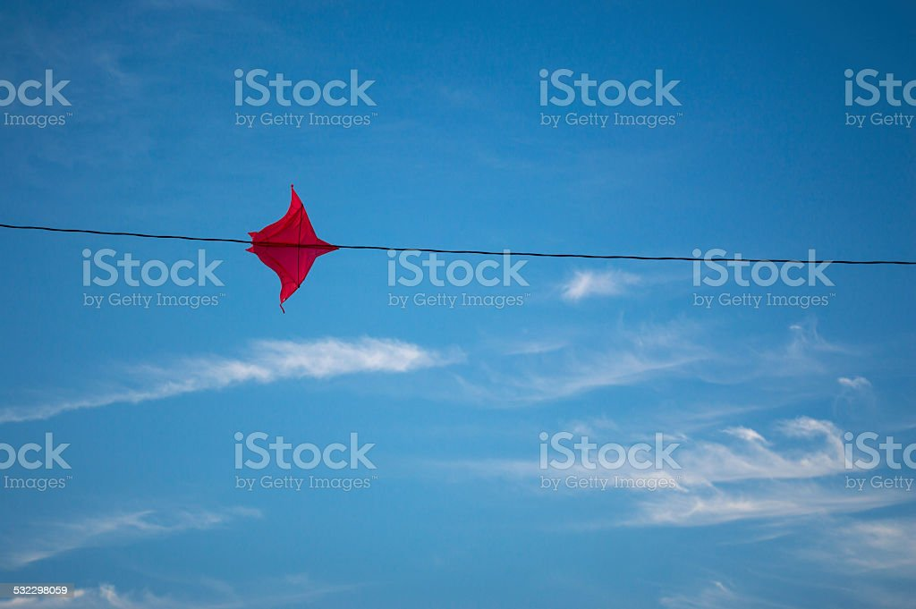 Kite stuck on a wire in the sky stock photo