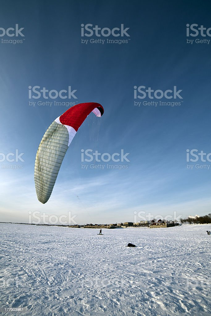Kiteboarder with blue kite on the snow stock photo