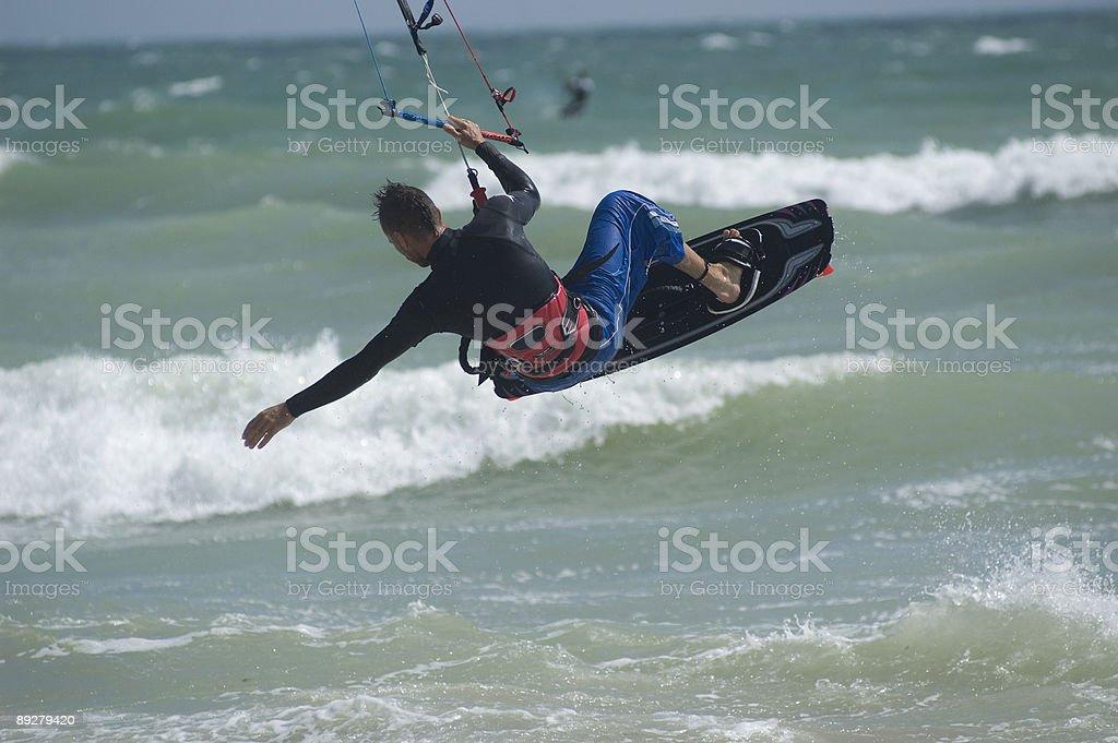 KiteSurfer jumping one handed stock photo