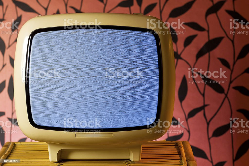 Kitschy retro style TV in front of pink floral wallpaper stock photo