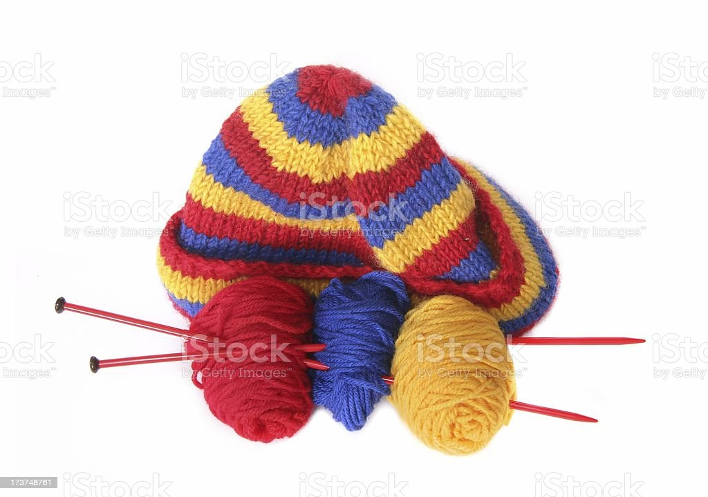 Kitted hat, needles and yarn on white. royalty-free stock photo