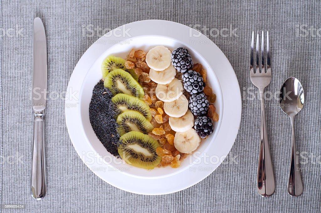 Kiwi banana dewberry raisin oatmeal smoothie bowl stock photo