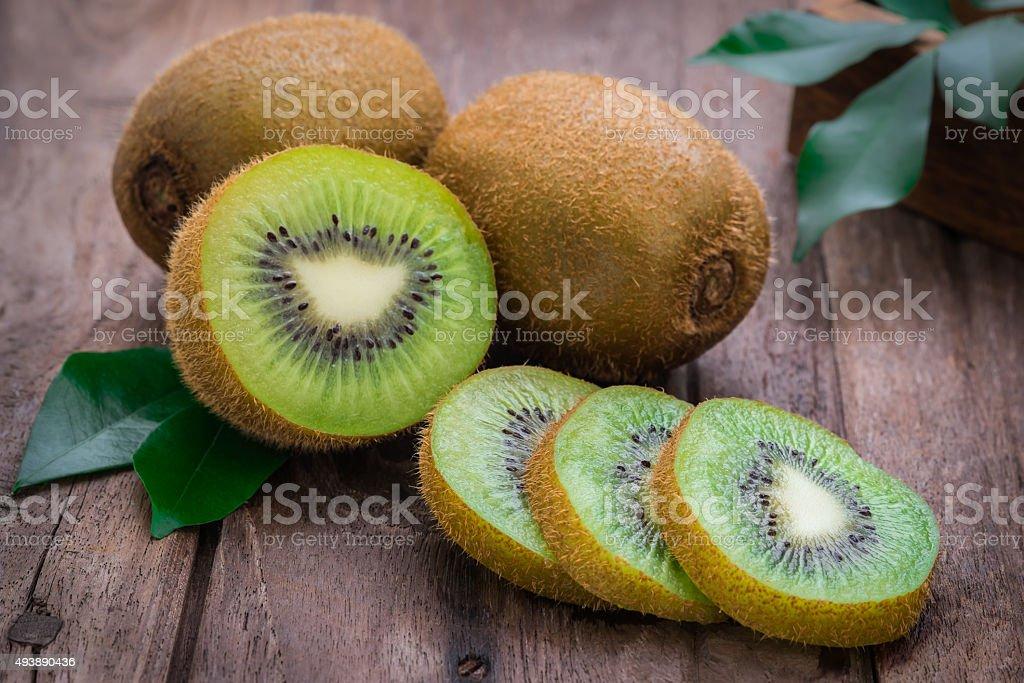 Kiwi fruit slices on wooden table stock photo