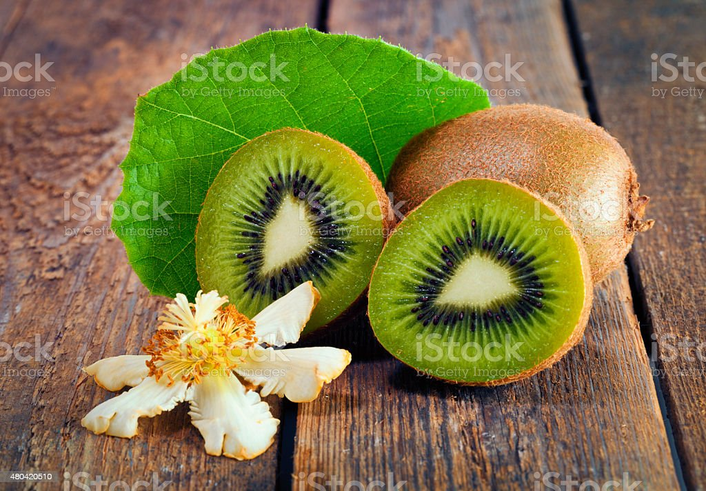 Kiwi fruits, blossom and leaf on rustic background stock photo