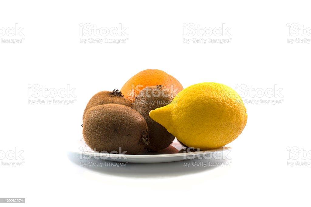 kiwi, lemon and orange, on a white plate stock photo