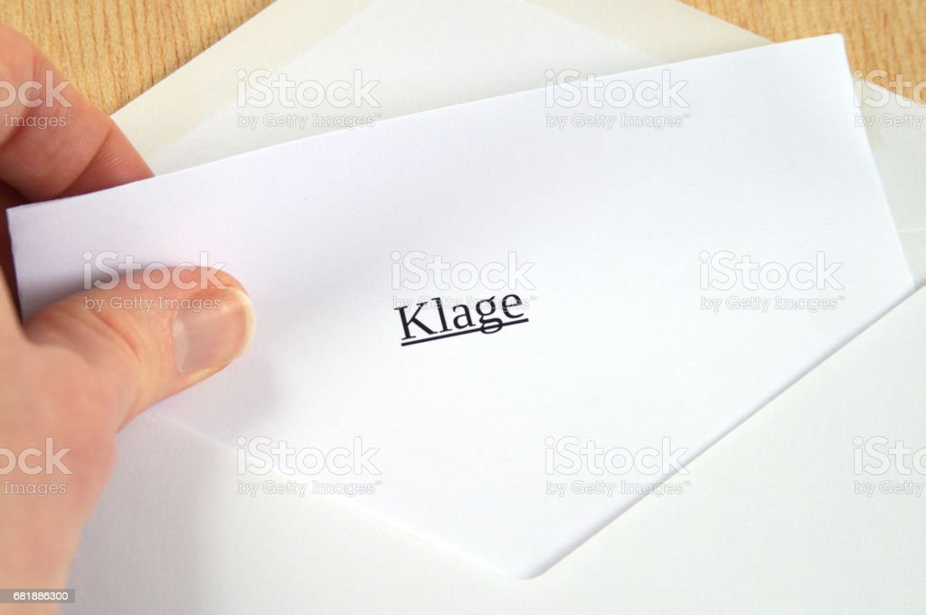 Klage (lawsuit) hand opening letter with printed word stock photo