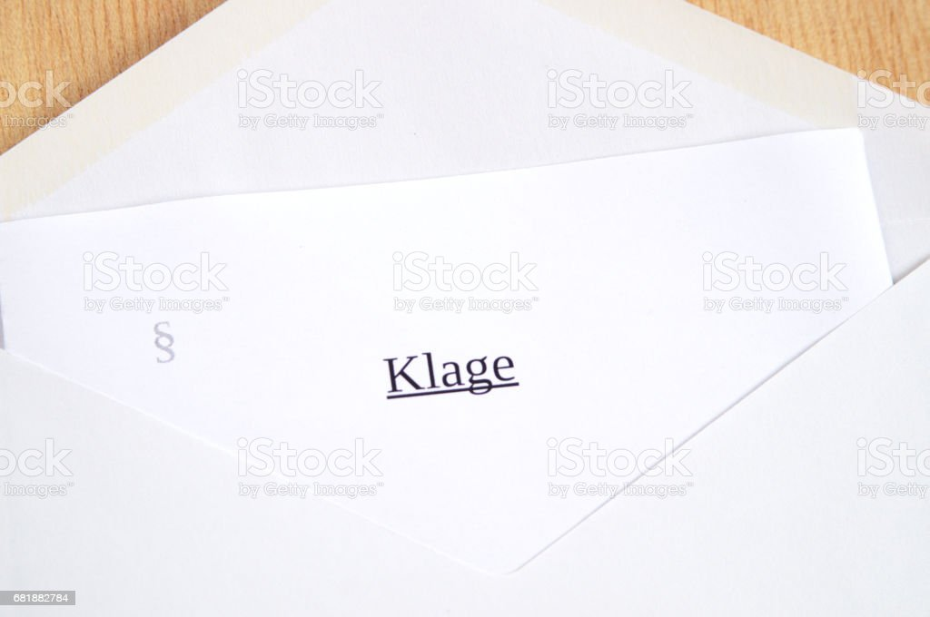 Klage (lawsuit) printed on white paper and envelope, wooden background stock photo