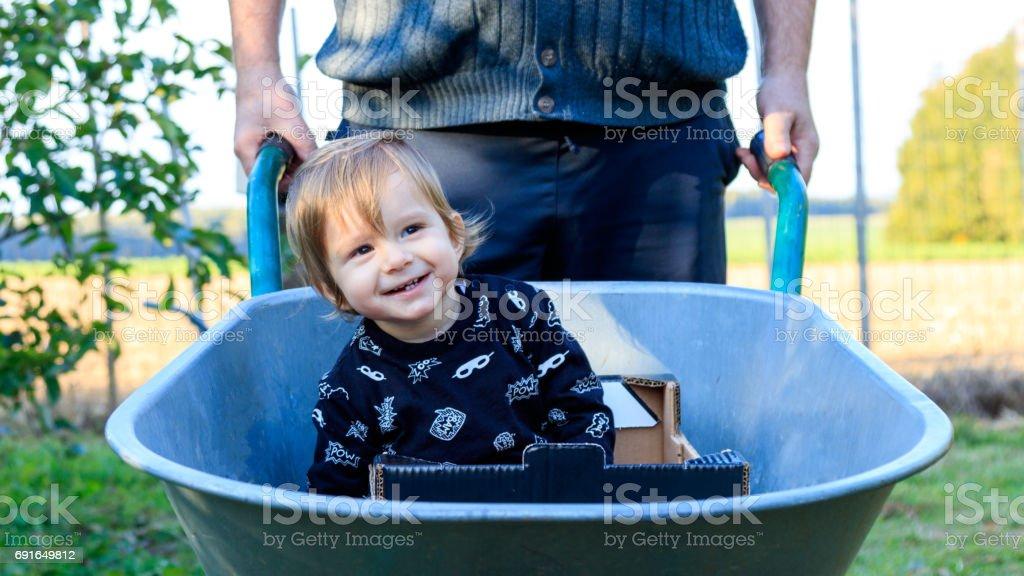 Kleines Kind in der Schubkarre stock photo
