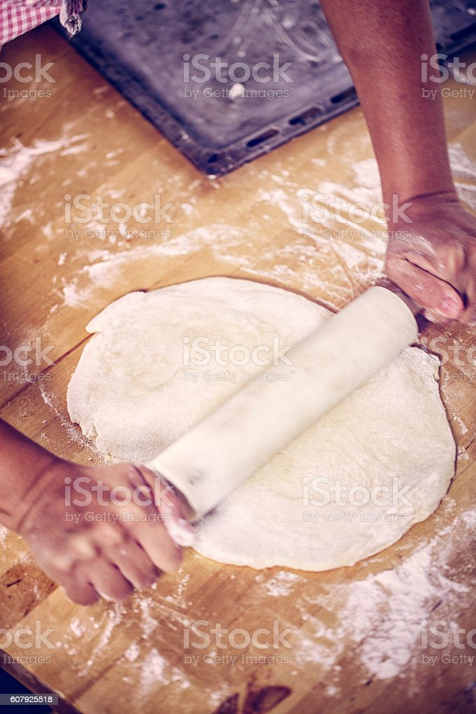 Kneading Dough with Rolling Pin On the Table stock photo