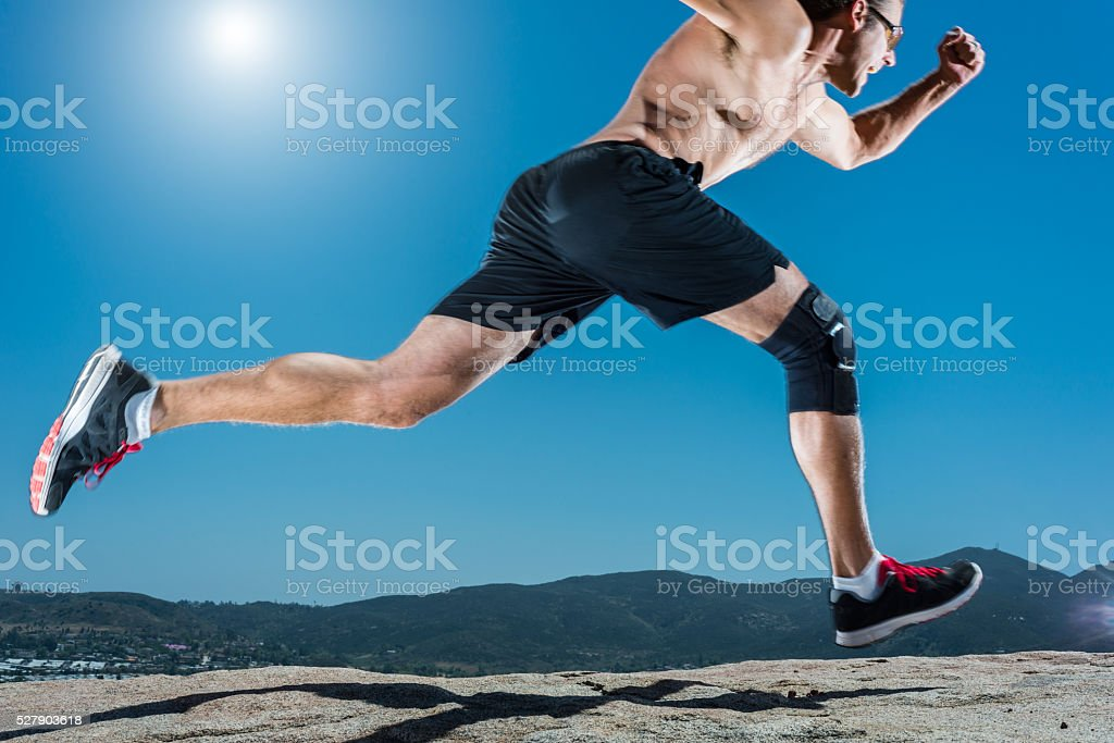 Knee Brace Running Up A Granite Boulder In The Mountains stock photo