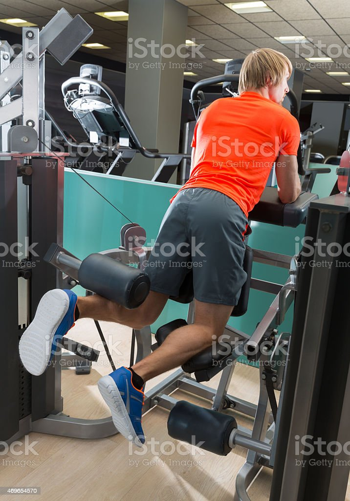 Kneeling leg femoral curl man at gym stock photo