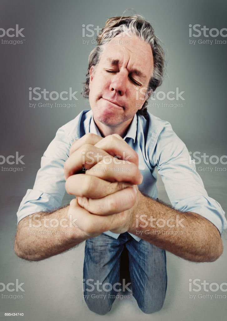 Kneeling man praying, seen from above with exaggerated perspective stock photo