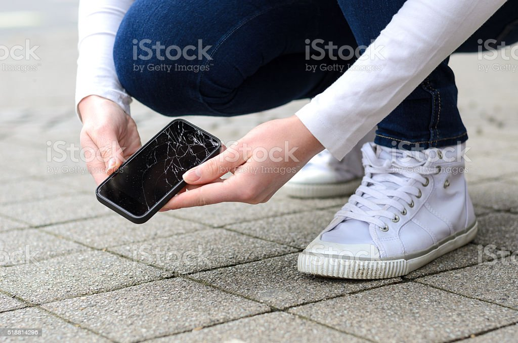 Kneeling person picking up broken phone on street stock photo
