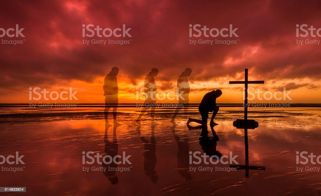 Kneeling Salvation Cross stock photo