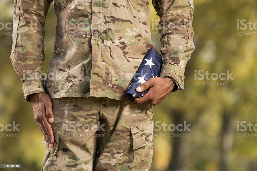 Kneeling Soldier Holding an American Flag royalty-free stock photo