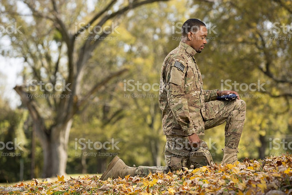 Kneeling Soldier Praying Over An American Flag royalty-free stock photo