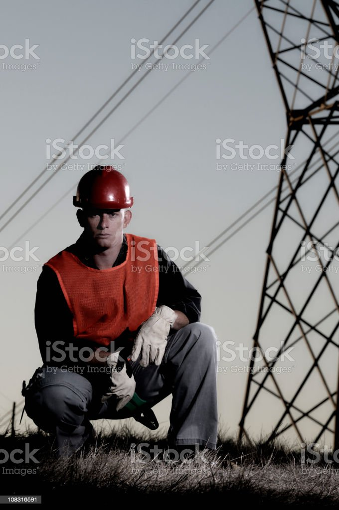 Kneeling utility worker against power lines royalty-free stock photo