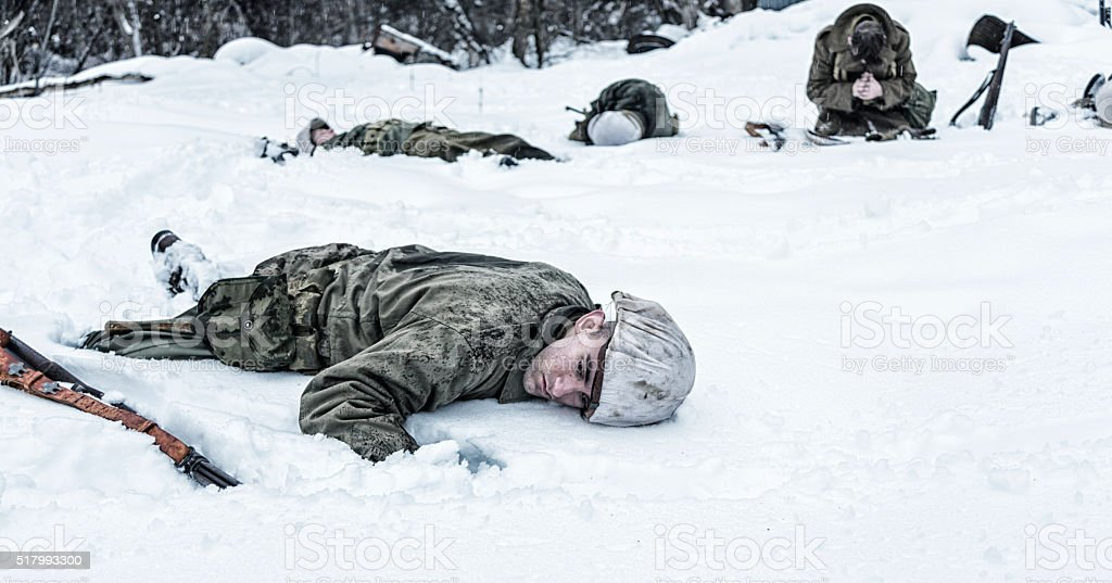 Kneeling WWII Soldier Praying For Dead Buddy War Casualties stock photo