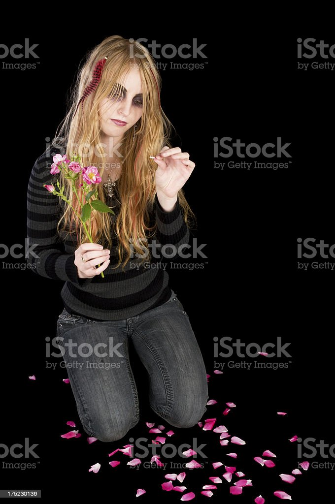 Kneeling young woman pulling petals off rose. royalty-free stock photo