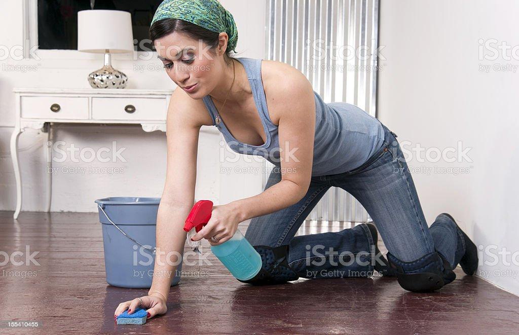 Kneepad Wearing Housekeeper Sprays Cleaner on Floor While Scrubbing stock photo