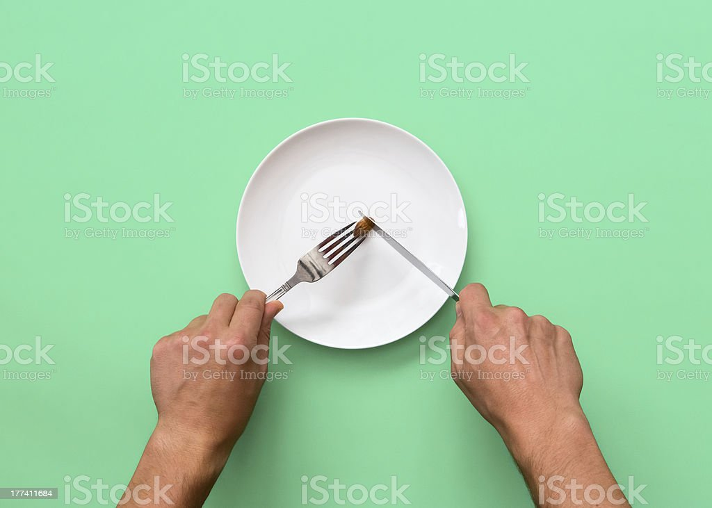 Knife and fork cutting into small diet meal on white plate stock photo