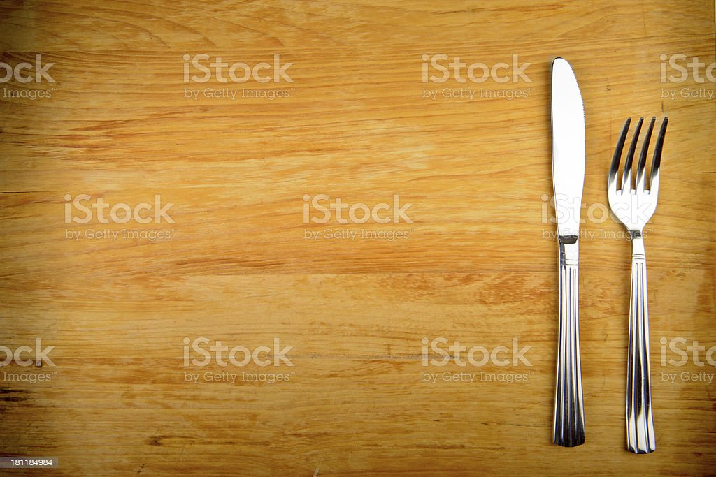 Knife and fork on an empty wood table stock photo