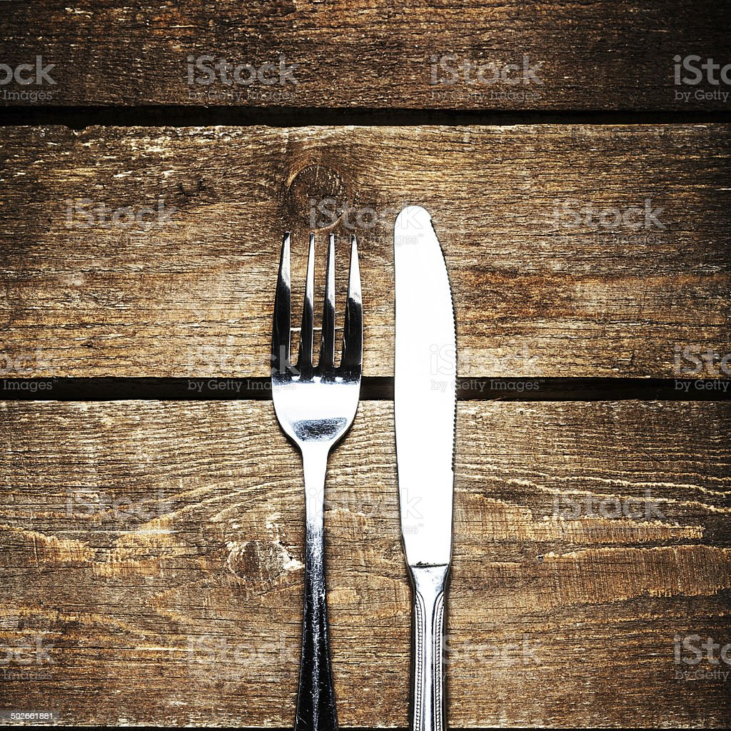 Knife and fork over wooden table with copy space. Diet stock photo