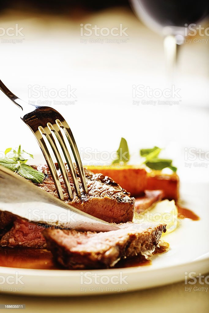 Knife and fork slice juicy steak, red wine in background royalty-free stock photo
