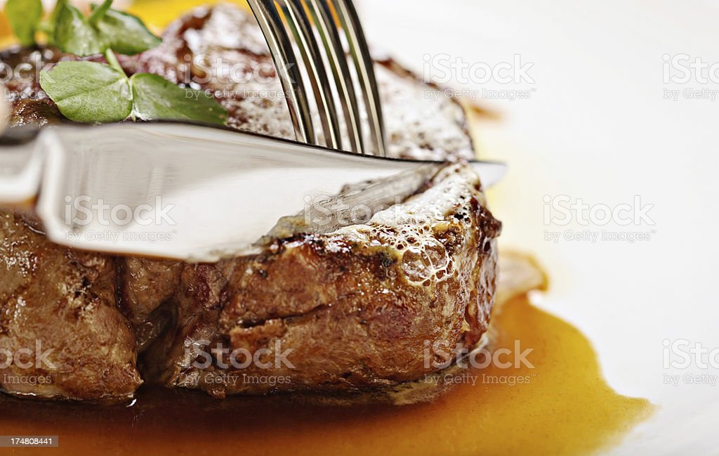 Knife and fork slice perfectly-grilled fillet steak stock photo