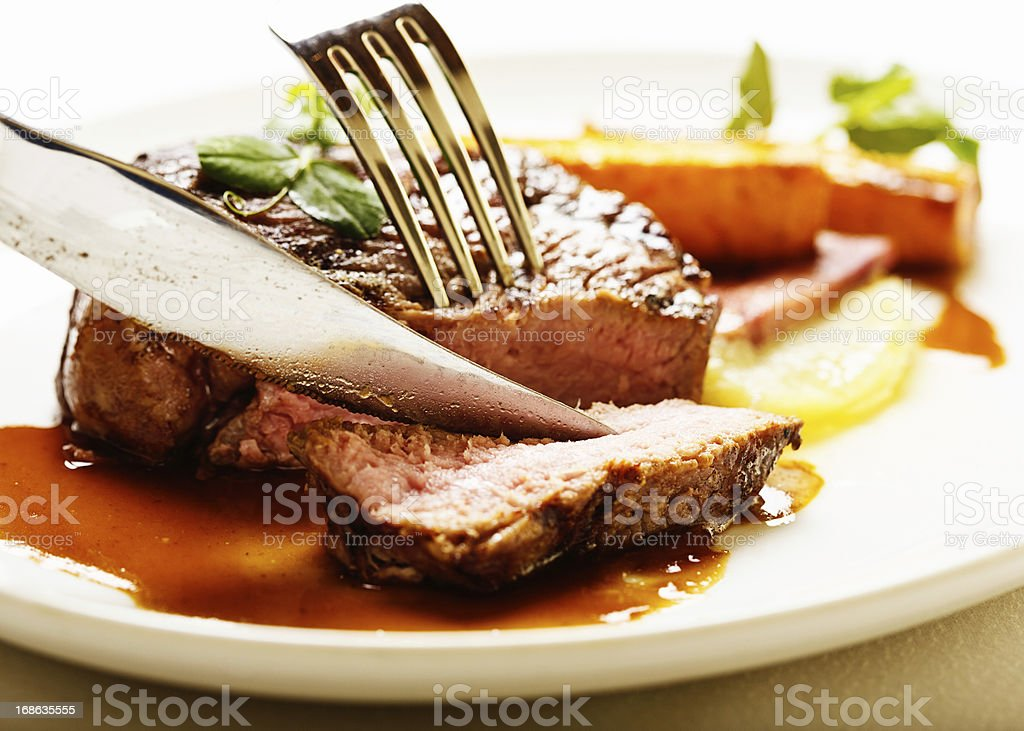 Knife and fork slicing into juicy grilled fillet steak stock photo